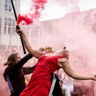 Female artistic performer with red smoke bomb bending backwards in a crowd in a bright red dress