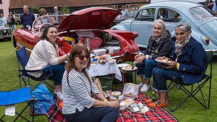 Four people sit around a chequered picnic blanket in front of a vintage car in Easton, Essex