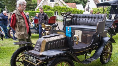 A man admires a very old vintage car from 1903 - a De Dion-Bouton - in Easton, Essex