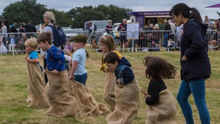 Six children bounce across a race track wearing sacks - a sack race at the Countess of Warwick's Show, Essex