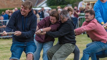 A team of adults pull on a rope as part of a tug of war at the Countess of Warwick's Show, Essex