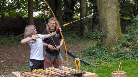 A child tries their hand at archery, firing an arrow into woodland at the Countess of Warwick's Show, Essex