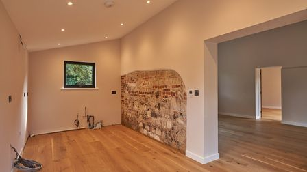 Modern light open-plan living space with oak floors, spotlights and exposed brick and flint wall
