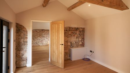 Open wood door leading from one reception room to another with no furniture, exposed brick and flint walls