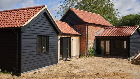 Barn conversion with multi-level roofs, featuring modern weather-boarded additions and original brick and flint barn