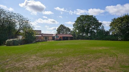 Large sweeping lawn with large barn conversion in the distance enclosed by hedge borders and trees