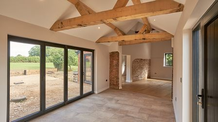 Open-plan living area with huge vaulted ceilings and exposed beams, patio doors leading out to garden