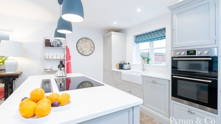 Modern white Shaker-style kitchen with huge central island with inset hob, eye-level electric oven and white Butler sink