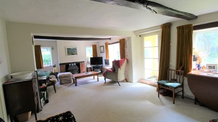 Large sitting room with exposed timber beams, brick built fireplace and carpeted floor with door to the porch