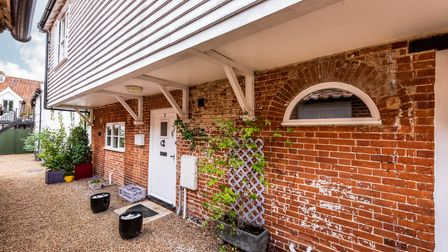 Front door to a partly brick, partly white weather-boarded house for sale in Hingham, Norfolk