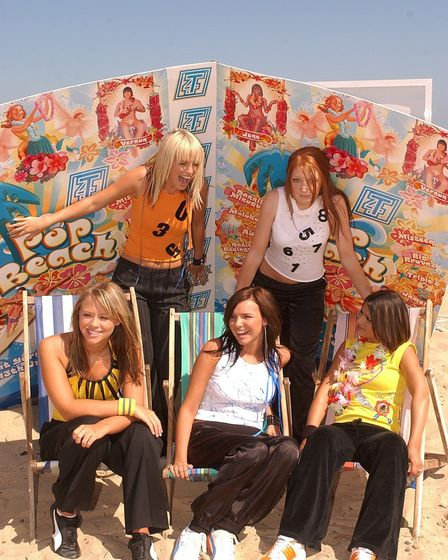 A wind break falls on Girls Aloud as they get ready for a photo call during Pop Beach 2003, in Great
