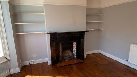 Reception room with Victorian feature fireplace, alcove shelving and wooden floors in a Norwich terrace house