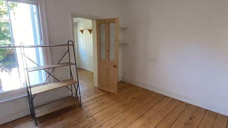 Reception room with white painted walls, wooden floors and door opening into rear lobby