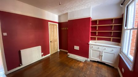 Large reception room with wooden floors, red-painted walls and built-in shelving in a Norwich terrace