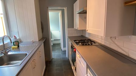 Modern grey and white galley style kitchen in a terrace property for sale in Norwich
