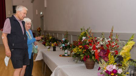 Man and woman admiring displays of flowers in vases and pots, Dunmow Horticultural Society, Great Dunmow