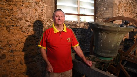 Paul Stannard with one of the bells at All Saints Church in Barrow