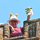 A man holds up a Yoda (from Star Wars) cuddly toy atop All Saints Church, Rayne