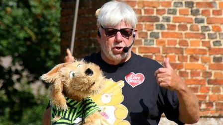A man holds up a large cuddly toy dog in Rayne, Essex