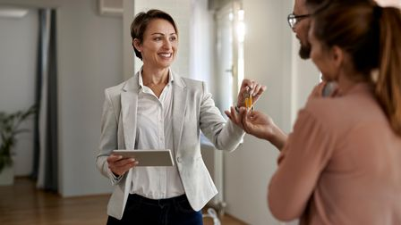 Young happy real estate agent giving house keys to a couple who is buying a new home.