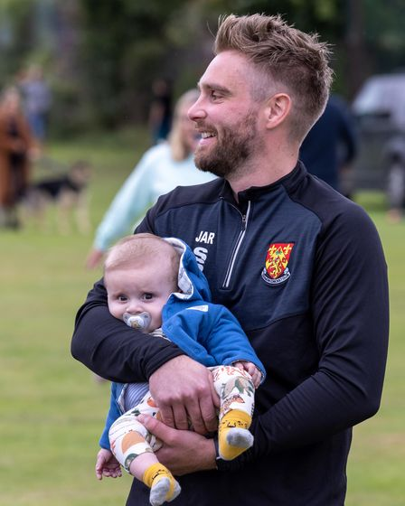 Man with a small child at Dunmow Cricket Club, Great Dunmow, Essex