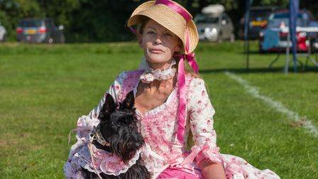 A woman in an elegant heritage pink dress and hat with ribbon, and dog dressed up, Felsted fun dog show, Essex