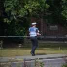 A police officer wearing a blue vest dealing with police tape in Felsted, Essex