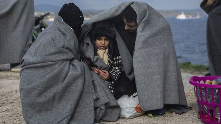 A family tries to keep warm with blankets, after the boat on which they crossed a part of the Aegean