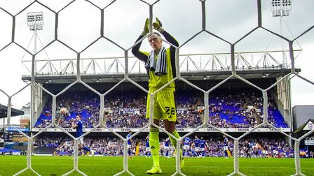 Christian Walton applauds fans as he takes his place in goal ahead of the game.
