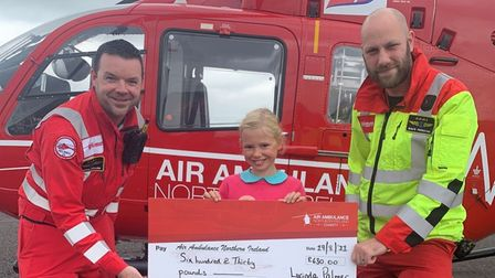 Lucinda of Felsted School, Essex, donating a giant cheque to personnel from Air Ambulance Northern Ireland