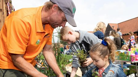 Matthew Jervis, from EGGrounds Care, showsyoungsters how to plant at Ellenor Fenn Garden