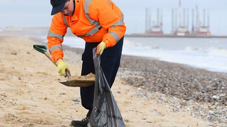 Cleaning up part of the beach at Gorleston after oil was found following a storm tide.Picture: James