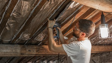 A man wearing safety goggles insulates the roof of his house with a drill