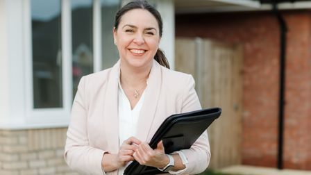 Rebecca Janman, director of Iceni Surveyors, standing holding a clipboard and smiling at the camera