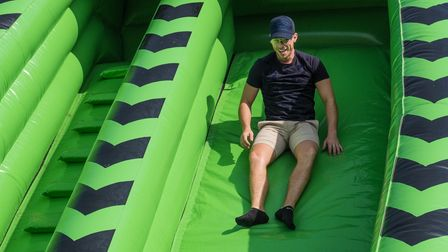 An adult man slides down a large green inflatable at the Flitch Green Fun Day 2021, Essex