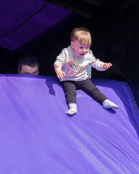 A baby on a small slide at the Flitch Green Fun Day 2021, Essex