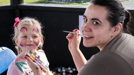 A woman paints a butterfly on a little girl's face a the Flitch Green Fun Day 2021