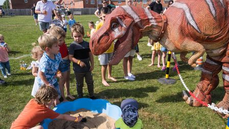 Children square up to an animatronic dinosaur at Flitch Green Fun Day 2021