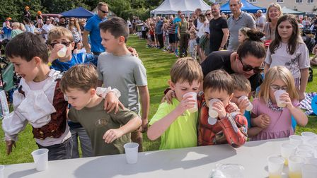 Thirsty children have a break after the run in the Finchingfield three-legged race 2021