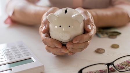 Old women's hands put money in the piggy Bank, the concept of retirement, savings.