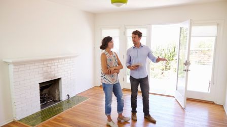 Male estate agent showing female buyer around an empty modern house