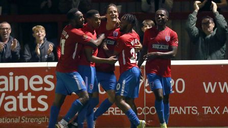 Will Wright of Dagenham and Redbridge scores the third goal for his team and celebrates with his tea