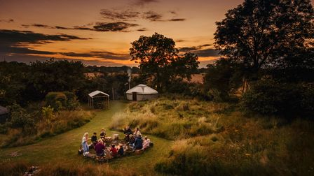Guests around the communal fire pit at Suffolk Yurt Holidays