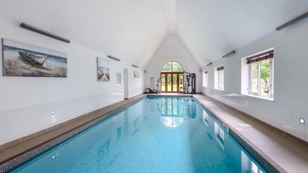 Indoor swimming pool in a white modern building which is for sale as part of a family home in Necton, Swaffham