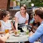 Waitress Serving Drinks To Group Of Friends Sitting At Table In Pub Garden Enjoying Drink Together