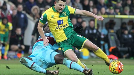 Norwich City midfielder Wes Hoolahan takes a tumble under the challenge of West Ham's Pedro Obiang.