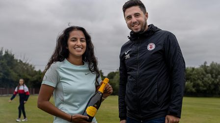 Woman with bottle of prosecco, man, smiling, Dunmow Cricket Club, Essex
