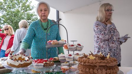 Women in front of a table with home made cakes for Macmillan fundraiser, Great Dunmow, Essex, September 2021