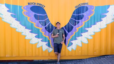 Jonny Manning, co-owner of Beach Street, poses in front of one of the attraction's murals