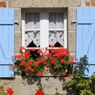Blue shutters and red flowers surround a window of a house in France